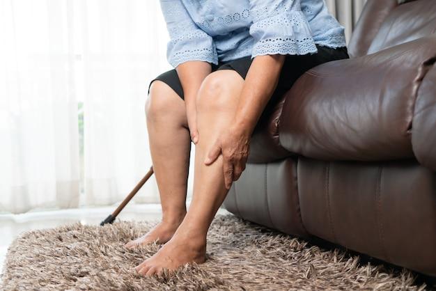 Dolore alle gambe della donna senior a casa, problema sanitario del concetto senior