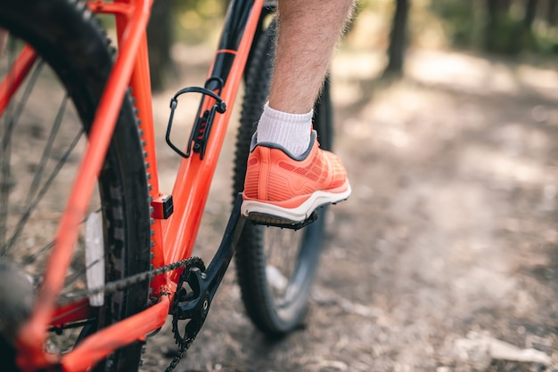Gamba in scarpe da ginnastica sul pedale della bicicletta durante la guida all'aperto