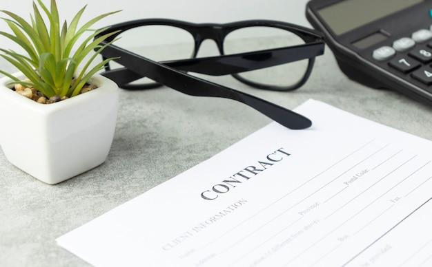 Firma del contratto legale con calcolatrice e bicchieri