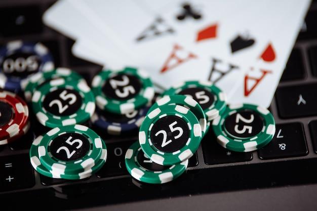 Regole legali per il concetto di gioco d'azzardo online. martelletto di legno, banconote di denaro e carte da gioco sulla tastiera del computer portatile.