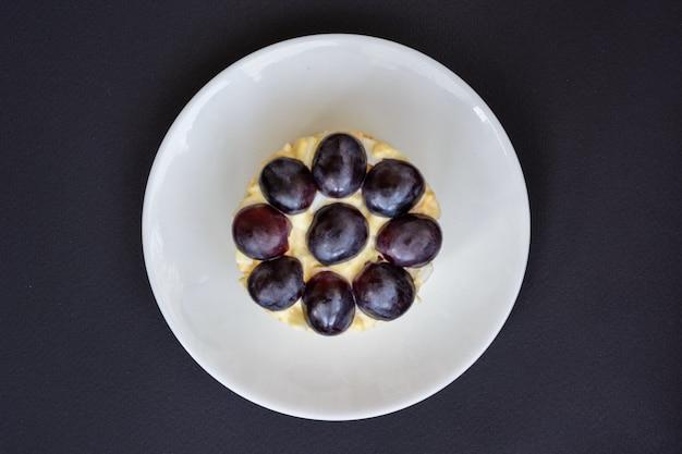La mitica insalata tiffany a strati con uva, pollo e formaggio su fondo nero. prende il nome dal soprannome della signora che ha pubblicato la ricetta dell'insalata sul portale culinario.
