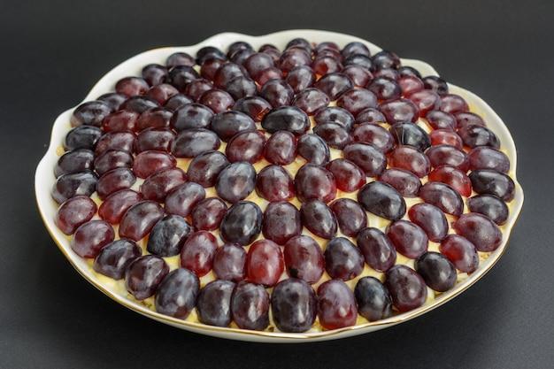 La mitica insalata a strati tiffany con uva, pollo e formaggio su fondo nero. prende il nome dal soprannome della signora che ha pubblicato la ricetta dell'insalata sul portale culinario.