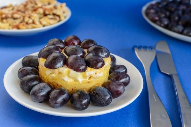 La mitica insalata tiffany a strati con uva, pollo e formaggio su fondo blu. prende il nome dal soprannome della signora che ha pubblicato la ricetta dell'insalata sul portale culinario.