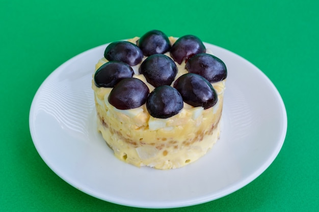 La mitica insalata a strati tiffany con uva, pollo e formaggio su fondo verde. prende il nome dal soprannome della signora che ha pubblicato la ricetta dell'insalata sul portale culinario.