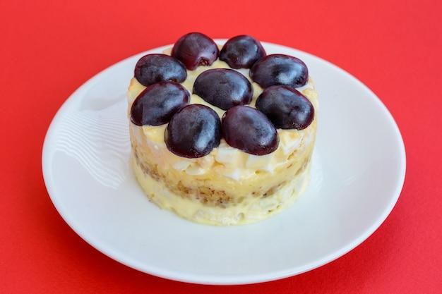 La mitica insalata tiffany a strati con uva, pollo e formaggio su fondo rosso. prende il nome dal soprannome della signora che ha pubblicato la ricetta dell'insalata sul portale culinario.