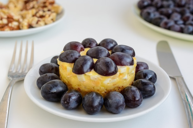 La mitica insalata tiffany a strati con uva, pollo e formaggio su fondo bianco. prende il nome dal soprannome della signora che ha pubblicato la ricetta dell'insalata sul portale culinario.