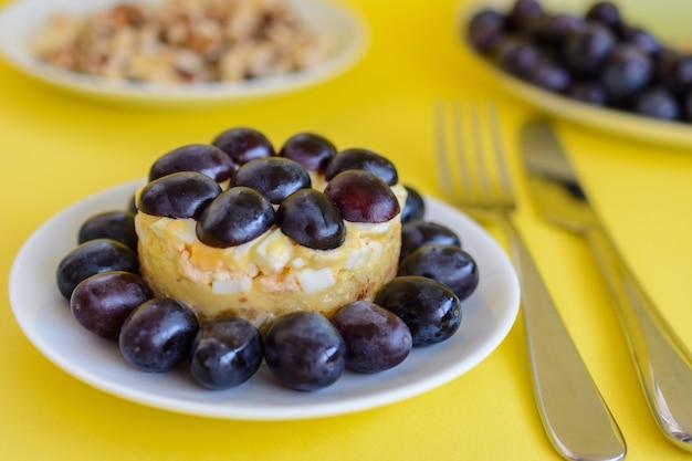 La mitica insalata a strati tiffany con uva, pollo e formaggio su fondo giallo. prende il nome dal soprannome della signora che ha pubblicato la ricetta dell'insalata sul portale culinario.