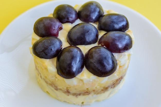 La mitica insalata a strati tiffany con uva, pollo e formaggio su fondo giallo. prende il nome dal soprannome della signora che ha pubblicato la ricetta dell'insalata sul portale culinario. Foto Premium