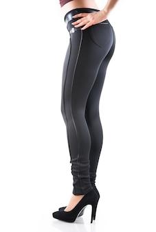 Gambe di una giovane e bella donna in leggings strappati sui tacchi