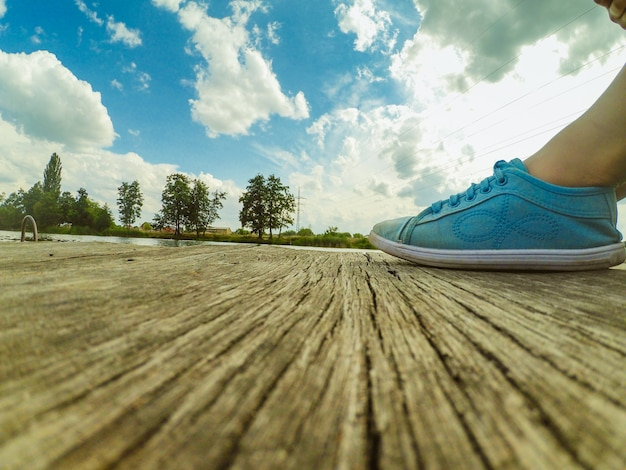 Gambe in mocassini blu su un molo di legno sullo sfondo di un cielo azzurro con nuvole bianche