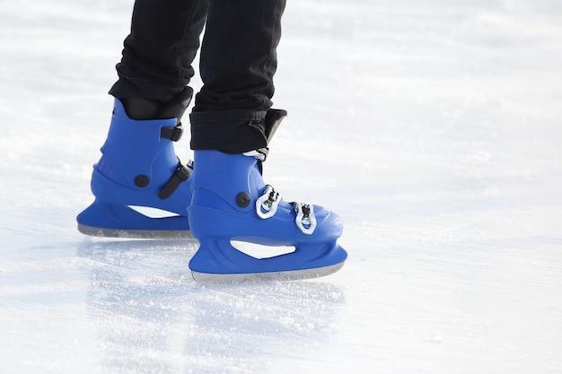 Gambe in pattinaggio blu sulla pista di pattinaggio