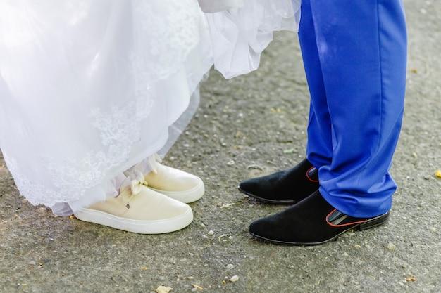 Gambe da sposa, sposo che indossa scarpe, scarpe da ginnastica della sposa alla cerimonia di nozze