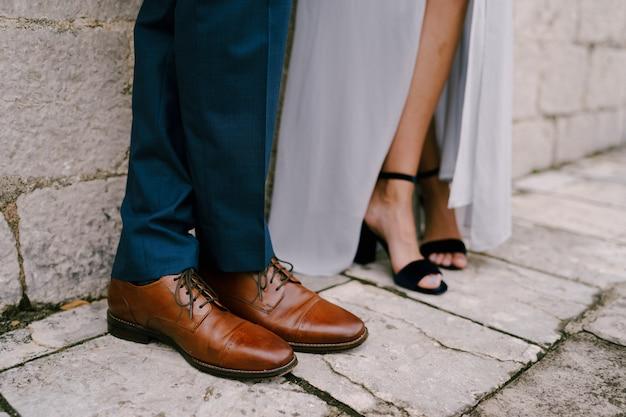 Gambe della sposa e dello sposo in primo piano delle scarpe da sposa