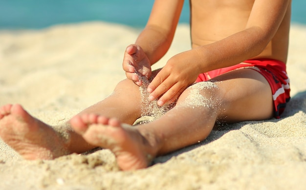 A gambe di un bambino sulla sabbia sulla spiaggia