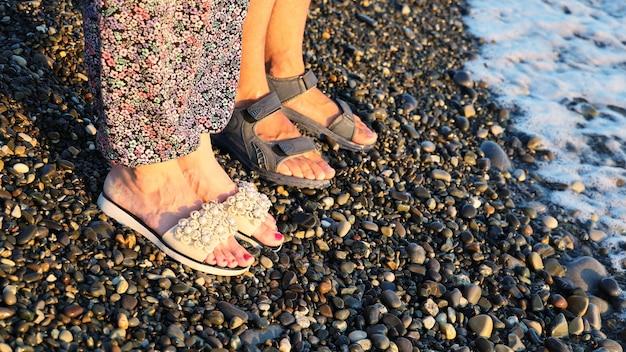 Le gambe della coppia in sandali stanno fianco a fianco sulla spiaggia di ciottoli al tramonto