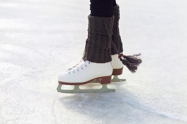 Le gambe dei pattini sono sul ghiaccio sulla pista. primo piano bianco classico dei pattini di figura. scaldamuscoli caldi lavorati a maglia con nappe