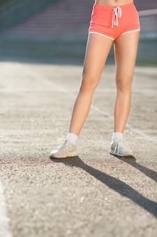 Gambe della ragazza in scarpe da ginnastica bianche e pantaloncini rosa in piedi sul terreno, senza volto, vista frontale. concetto di sport, abbigliamento sportivo, stadio