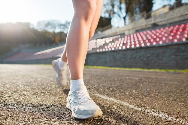 Gambe di ragazza in scarpe da ginnastica bianche e calzini in esecuzione in pista, senza volto, vista posteriore. concetto di sport, abbigliamento sportivo, stadio con luce solare