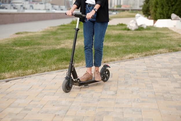 Gambe e mani di giovane donna contemporanea in abbigliamento casual in piedi su uno scooter elettrico mentre si muove lungo la strada urbana per andare al lavoro