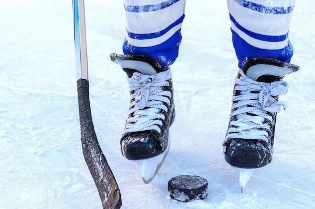 Le gambe del giocatore di hockey, bastone e rondella close-up.