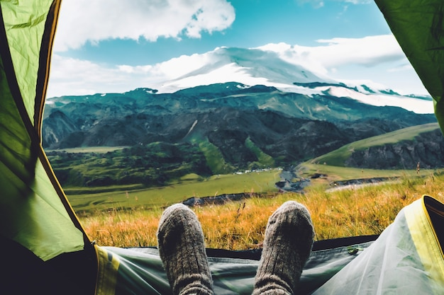 Gambe in calze di lana grigie lavorate a maglia con vista mattutina dalla tenda sulle montagne del caucaso
