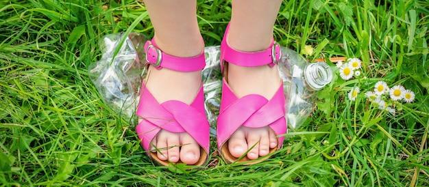 Le gambe di una bambina calpesta una bottiglia di plastica sull'erba verde del parco