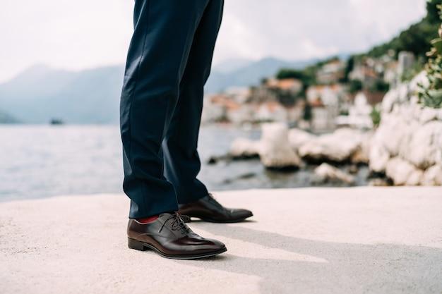 Gambe di un uomo in pantaloni blu e scarpe marroni in piedi sul primo piano del molo