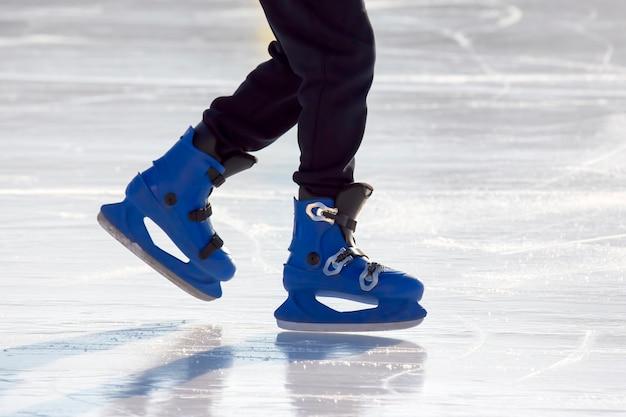 Gambe di un uomo in pattini blu cavalca su una pista di pattinaggio. hobby e tempo libero. sport invernali