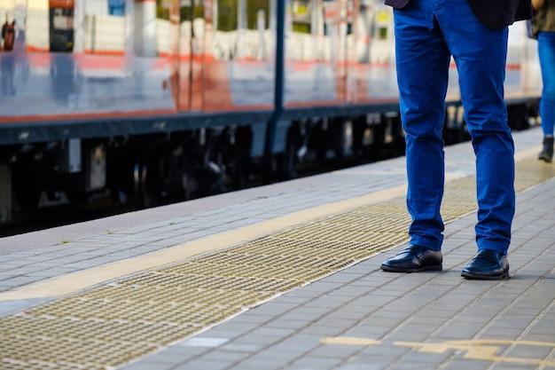 Gambe di un uomo con pantaloni blu acceso e scarpe di pelle nera, in piedi sul binario della stazione ferroviaria contro il tavolo di un treno in arrivo.
