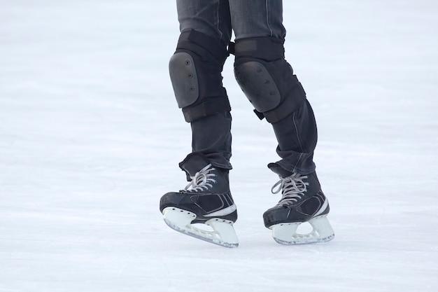 Gambe di un uomo che pattina su una pista di pattinaggio sul ghiaccio. hobby e sport. vacanze e attività invernali.