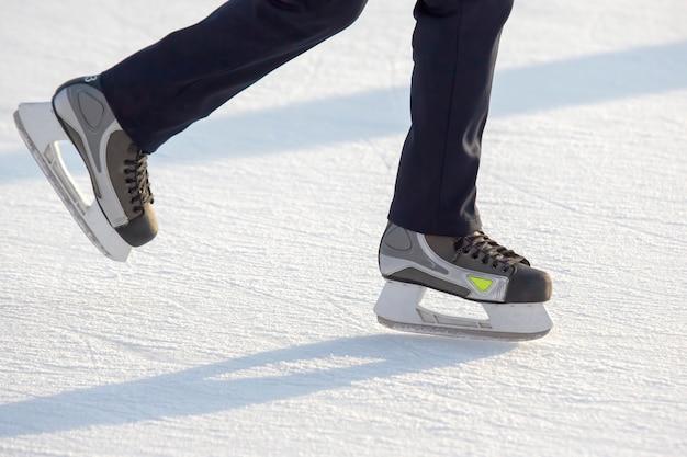 Gambe di un uomo che pattina su una pista di pattinaggio sul ghiaccio. hobby e sport. vacanze e attività invernali