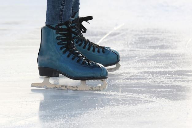 Gambe di un uomo che pattina su una pista di pattinaggio sul ghiaccio.