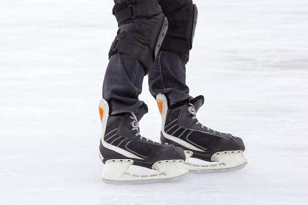 Gambe di un uomo che pattina su una pista di pattinaggio sul ghiaccio