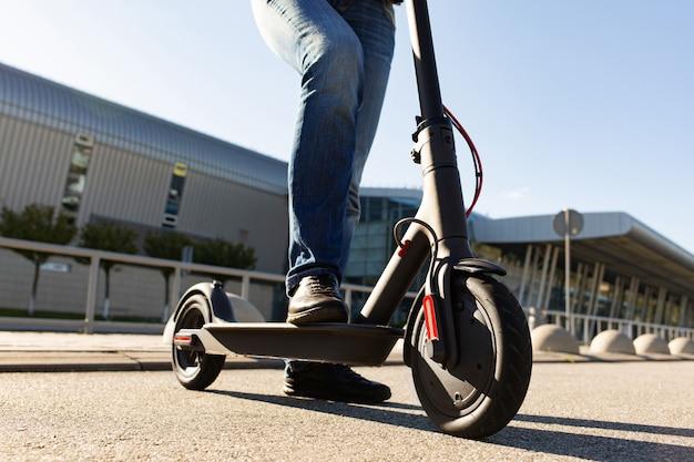 Le gambe di un uomo che sta sul motorino elettronico hanno parcheggiato sul marciapiede al paesaggio urbano sul tramonto. trasporto urbano alla moda su moderni scooter elettrici. concetto di mobilità eco-compatibile.