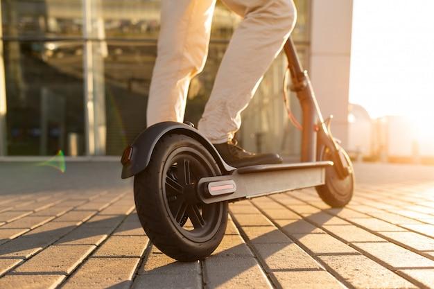 Le gambe di un uomo in piedi su uno scooter elettrico parcheggiato sul marciapiede