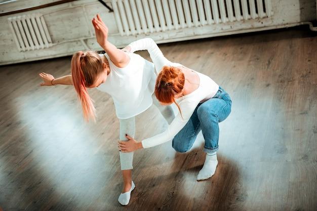 Posizione delle gambe. insegnante professionista di danza moderna con capelli rossi che indossa jeans che correggono la posizione delle gambe del suo studente