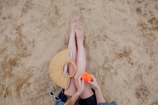Protezione delle gambe dai raggi uv del sole mettendo crema solare crema solare