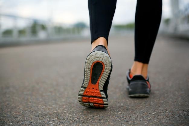 Gambe di una ragazza sportiva in esecuzione in scarpe da ginnastica, tacco rialzato. suola della scarpa
