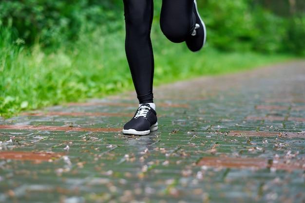 Le gambe della donna corrente che atletic spotman si allena nel parco dell'estate. ritratto di fitness all'aperto dopo la pioggia