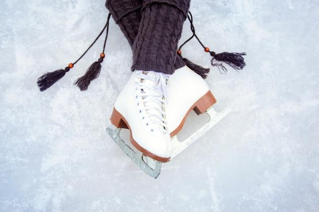 Gambe calzate con pattini da pattinaggio artistico bianchi. bella la posa delle gambe sulla pista di pattinaggio. caldi scaldamuscoli in maglia con nappine e pattini classici