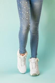 Gambe di una ragazza snella in jeans attillati e scarpe da ginnastica calde bianche. stile sportivo invernale.