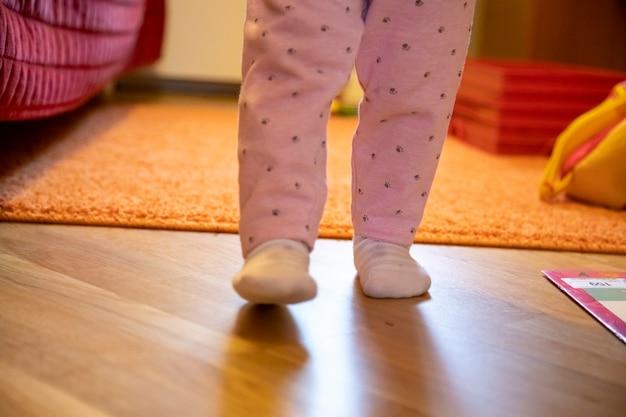 Le gambe di un bambino piccolo camminano per la stanza. concetto di primi passi del bambino. senza volto. felice genitorialità