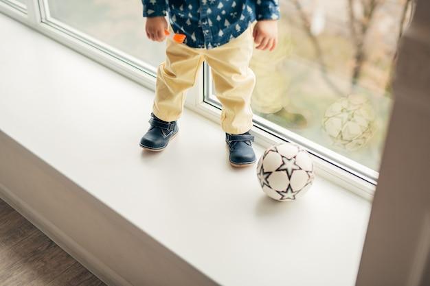 Le gambe un bambino piccolo che gioca a palla