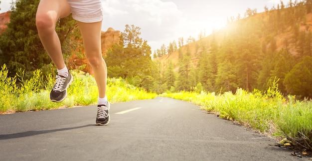 Gambe in scarpe sportive su strada all'alba.