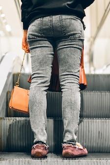 Gambe in piedi sulla scala mobile di un centro commerciale