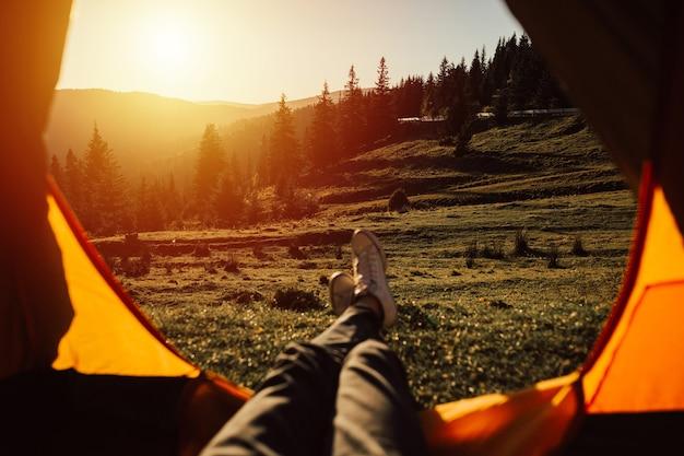 Gambe del viaggiatore in una tenda all'aperto. uomo che si distende in tenda in montagna