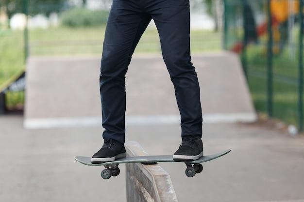 Gambe di un giovane sconosciuto in jeans neri e scarpe da ginnastica su skateboard mentre si eseguono trucchi complicati nel parco soleggiato estivo