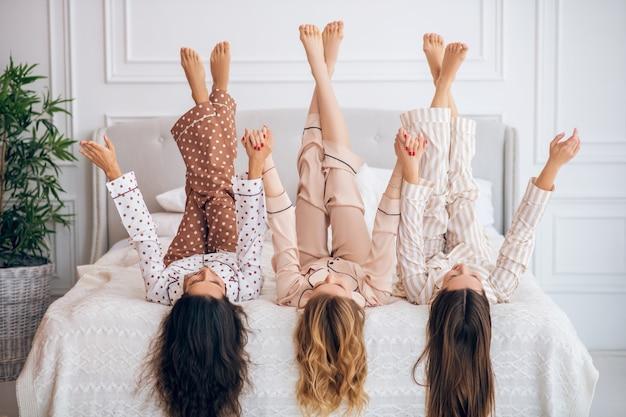 Gambe in alto. tre ragazze in pigiama sdraiato sul letto con le gambe alzate