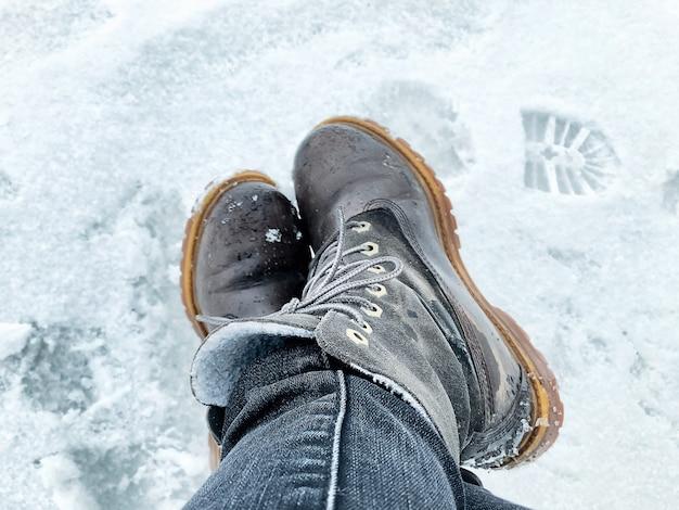 Gambe in stivali invernali caldi sulla superficie innevata