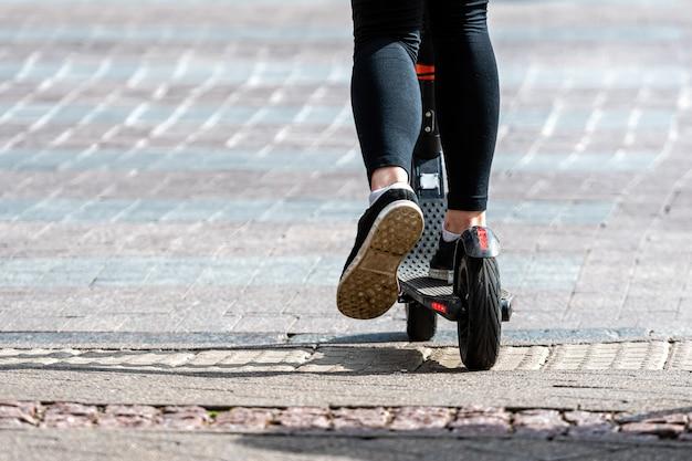 Gambe di una donna su un monopattino elettrico